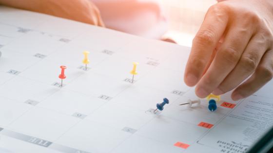 Hand steckt Pins auf einen Kalender; daneben steht ein Laptop