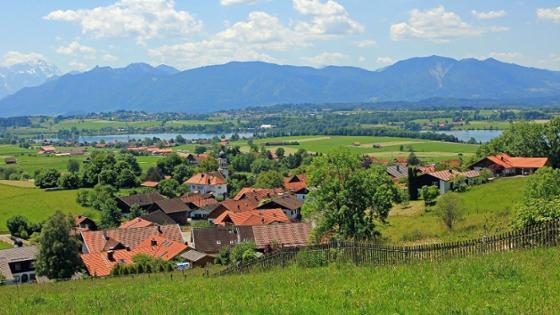 ein Dorf - im HIntergrund ein See und Berge
