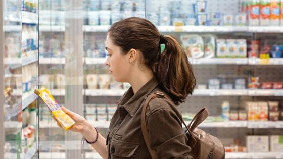 A woman in a supermarket is reading the label of a food item