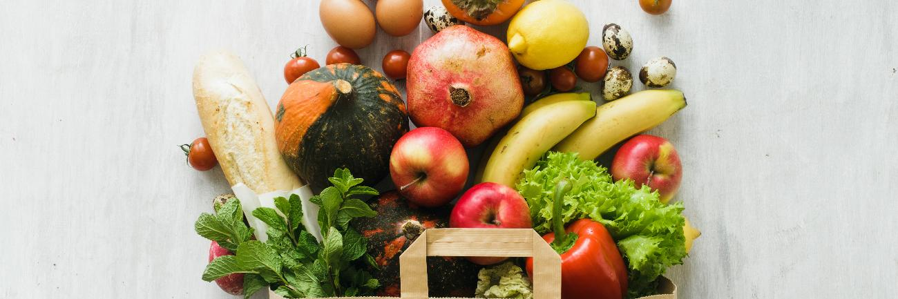 Various foods in a paper bag: fruits, vegetables, eggs, bread