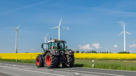 A tractor is driving on a road. In the background is a canola field and wind power plants