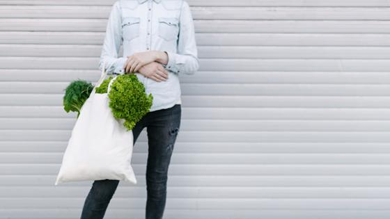 A woman is holding a fabric bag filled with vegetables in her hands