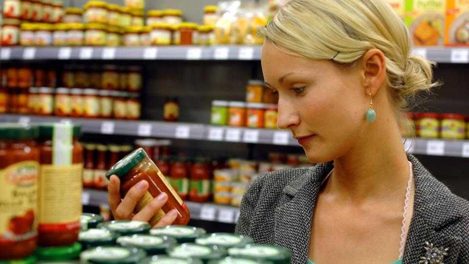 Woman looks at a product in a supermarket