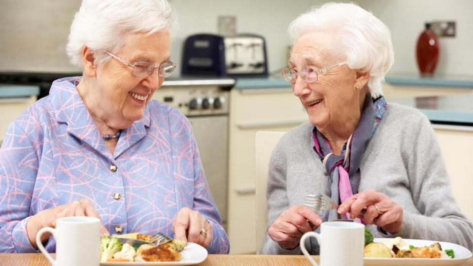 Two senior women eating at a table