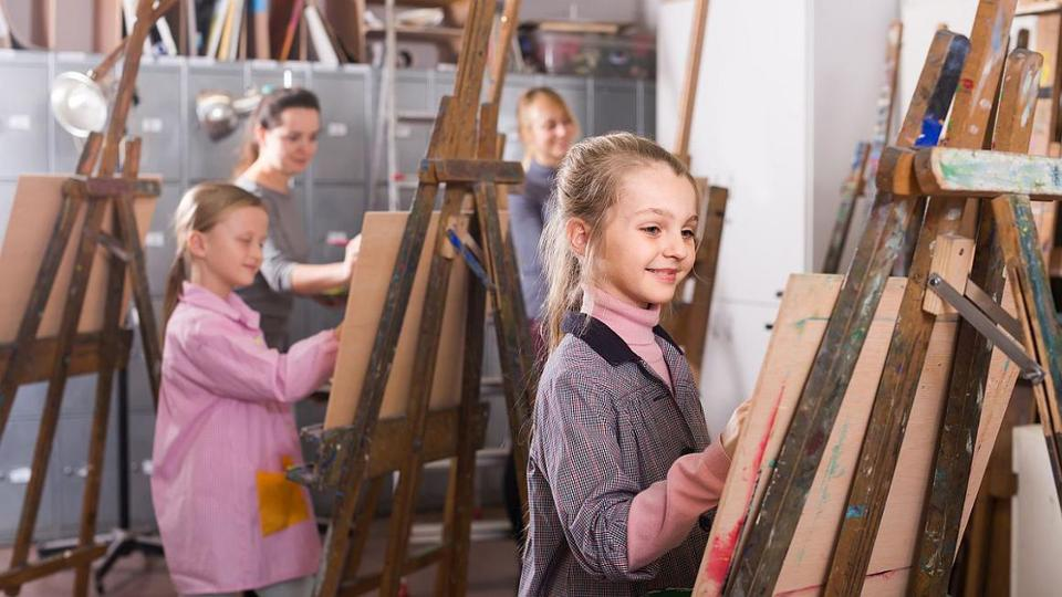 Two girls and two women are standing in front of their easels and paint