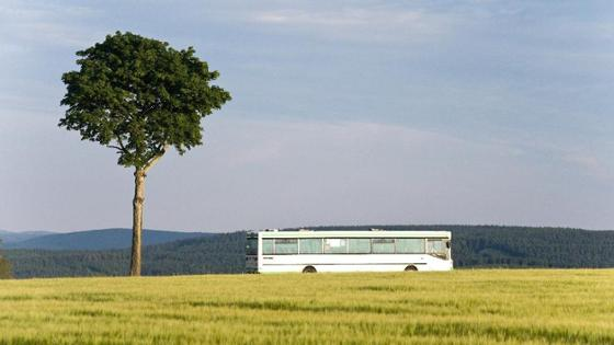 A bus passes a field in the country.