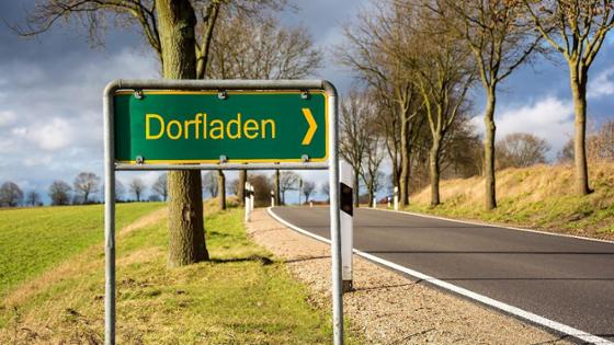 "The street sign ""Dorfladen"" can be seen in front of a country road."